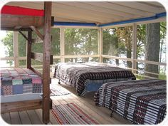 Sleeping porch with four beds by lake