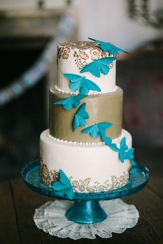 wedding cake with teal paper moths, photo by Joe+Kathrina http://ruffledblog.com/whimsical-san-juan-capistrano-wedding #weddingcake #cakes #whimsy