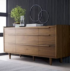 Our 1960s-inspired Tate collection recalls the timelessness of mid-century design with tailored profiles and streamlined shapes. Crafted of solid American walnut and walnut veneer, Tate showcases gallery fronts and linear undercut drawer pulls supported by tapered turned legs.