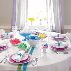 Turn the tables on traditional Easter pastels by choosing a vibrant palette for plates and decorative ribbon. A centerpiece of bowls filled with dyed eggs looks dramatic sitting atop white linen. - FamilyCircle.com