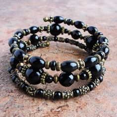 This stylish memory-wire bracelet was handcrafted with authentic Black Onyx gemstone well-polished high quality beads. I have added antiqued brass finish pewter beads and spacers to embellish and create a gorgeous vintage look. The soft memory-wire makes this bracelet easy to put on and very comfortable to wear. All metal materials are lead-safe. Great for casual to semi-formal. Size: One size fits all wrists from small to large Condition: new Materials: Black Onyx (4-10mm round, 8mm…