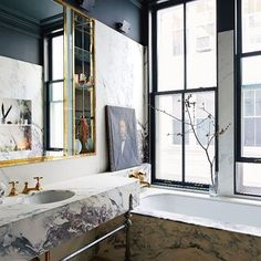 Master Bath INspo // master bathroom in #JennaLyons's SoHo loft features a Breccia Capraia marble-clad tub and vanity. One of the details Lyons is most proud of is the series of bronze table legs that support the vanity, designed by jeweler Philip Crangi (@gilesandbrother). As baroquely detailed as the hilt of a medieval sword, they were cast directly from his life-size, hand-drawn renderings. Photo by Simon Watson (@simonpwatson).
