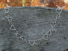 Silver Heart Necklace  This is a dainty and delicate sterling silver Necklace where the hearts are created individually and then soldered together, meaning each heart will be slightly different and each necklace unique. With Valentine's Day coming this would be a nice present for someone special.  It is approximately 45-46 cm long and as you can close it to any heart it's also adjustable. As you can see in the pictures I also make a matching heart bracelet, which is listed separately. The…