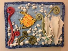 kids clay projects at the Ceramic League of Miami. made with slabs. Pieces are not scored and slipped on. Work is fired, then pieces are removed, glazed, then placed  where they will stay, then fire again. When glazing apply plenty of glaze on the back of the work so when the glaze melts they stick in place.  Fire flat.  This method gives a nice clean look.