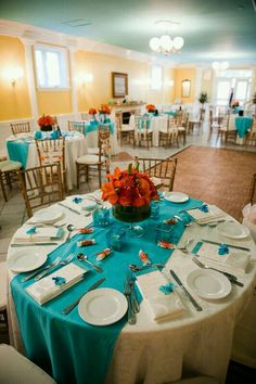 white linen table cloth with teal runners, with colorful coral flower centerpieces