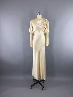Originally worn in Light champagne bias cut rayon duchesse satin with cowl neckline and full leg o'mutton sleeves. Attached satin half-belt in back with sil Vintage Vogue, Vintage Fashion, 1930s Fashion, Vintage Style, New Wedding Dresses, Gown Wedding, Wedding Wear, Vintage Dresses, Vintage Outfits
