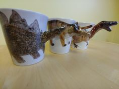 Nothing cozier than sipping hot chocolate from a mug (especially ones where the handles are the dinosaur heads!) From left to right: You can regale all your relatives with more facts about all these by listening to our Dinosaur Head, Dinosaur Gifts, Dinosaurs, Hot Chocolate, Happy Holidays, Facts, Canning, Mugs, Shelf