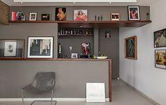 """A moldura de imbuia cobre o balcão, entre a sala e a cozinha, e segue como prateleira pelas paredes. """"Como o morador tem muitos quadros, pode apoiá-los nela e trocá-los à vontade"""", diz o arquiteto Gustavo Calazans. Dentro da cozinha, também há obras."""
