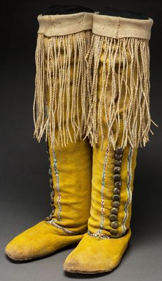 A pair of Comanche woman's beaded & fringed hide boots (circa 1900) Painted overall in yellow ocher pigment, with narrow lanes of small geometric motifs finely stitched in various shards of glass beads, trimmed with small silver buttons & twisted hide fringe.  Rawhide soles.
