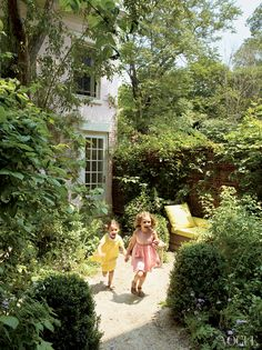 """Both daughters bounding through Brooks's abundant plantings. """"I have so little garden, and I have to try everything,"""" she says."""