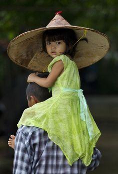 fotojournalismus:  A child is carried by an adult in Khanaung Chaung Wa village, southeast of Yangon, Myanmar on June 5, 2013. [Credit: Gemunu Amarasinghe/AP]