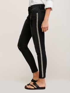 Black Studded Skinny Jeans | This edgy distressed skinny jeans are featured in a low-rise fit with rock-inspired metal stud detailing down the sides. Five-pocket style with a zip fly and button closure.
