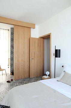 Parfaitement intégrée au reste de la maison, la petite extension transformée en suite à laquelle on accède par un couloir organisé en placards. Une paroi coulissante en chêne privatise la douche.