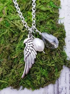 Lovely handmade angel wing charm necklace with genuine baroque sea pearl and crystal bead. Light catching crystal glistens in the light. This makes a great gift of love or as a memorial necklace. Wing pendant is one inch long and is set on a 18 inch chain with a 2 inch extender for extra length. The size is just right - not too dainty but not overbearing. A beautiful, timeless piece to cherish throughout the years.  *Message me for a complimentary paw charm if this is a pet memorial…