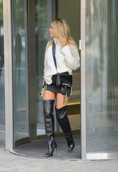 Blonde in black thigh boots street style.
