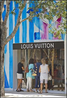 Shoppers peer in the window at the Louis Vuitton store in the Design District.