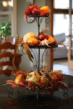 Fill a tieres stand with Autumns Treasures, leaves, gourds, fruit and embellishments for a Thanksgiving table