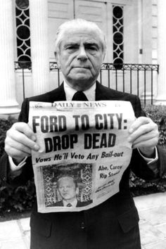 """Throughout the 1970s, NYC teetered on bankruptcy, which was avoided by deep reduction in police, fireman and teachers. In the above photograph, then Mayor Beame holds up a newspaper with the headline 'Ford to City: Drop Dead,"""" following President Fords's refusal to use federal funds to bailout NYC."""