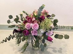 Loose, overflowing garden bouquet with hellebore, roses, mums, tulips, dusty miller, Queen Ann's Lace, silver dollar eucalyptus and baby blue eucalyptus.