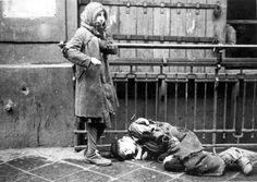 Warsaw, Poland, A boy lying on the pavement in the ghetto with a girl standing next to him.