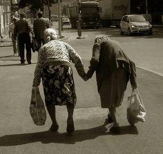 Two elderly women holding hands crossing street.