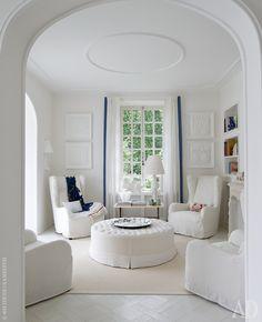 Гостиная дома на озере Комо, спроектированного Барбарой Фалангой. Мебель обтянута чехлами из белого льна. На стенах декор в виде гипсовых слепков.