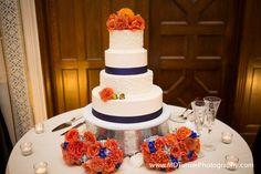 Beautiful white cake with orange flower accents and blue ribbon - Houston wedding photography - MD Turner Photography