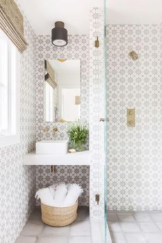 Alyssa Rosenheck - Amanda Barnes Interior Design - Beautifully fitted white and gray bathroom boasts a floating sink vanity fitted with a white porcelain square sink mounted beneath an antique brass wall mount faucet.