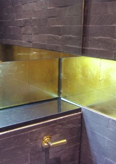 DecoGild luxury gold glass splashback created using a distressed gilding technique.