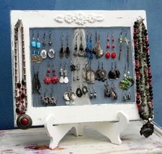 This is a 2 parts earrings hanger. A fine, strong plastic mesh inserted in a painted wood frame, standing on a stable two legs wood stand   It can hold between 25-40 pairs of earrings of all kinds and 6-10 necklaces.