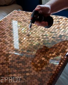 Pennies encapsulated in bartop epoxy. Heat it with a propane torch while still wet to remove bubbles.