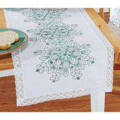 """Green Ornament Table Runner Stamped Embroidery Kit by Nob Hill. $34.99. Cool shades of green edged with lace will complement almost any room. Stamped for embroidery on white 100% cotton fabric with a lace edge. Kit includes cotton floss, needle, and instructions. Approximately 16 x 36"""" (41 x 91cm). Imported from Europe."""