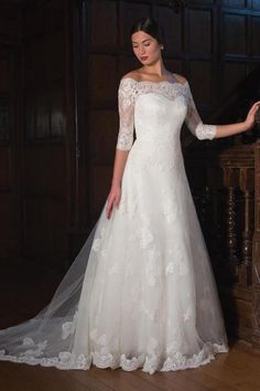 Wedding dress - Augusta Jones | An off-shoulder full A-line lace gown with an illusion lace back. Features covered buttons and a translucent lace skirt with train.