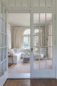 Gorgeous home features interior French doors with transom windows open to a living room featuring a white slipcovered sectional lined with blue pillows facing a nickel and mirror coffee table illuminated by a gold leaf faux bois floor lamp.