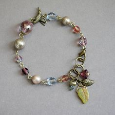 Multicolor Glass and Pearl Beaded Bracelet, Bronze Bird and Leaf Charm, Czech Glass, Pearl and Swarovski Crystal Bracelet Used Materials and Measurements * red luster faceted czech glass -- 12mm * swarovski and glass pearl -- 3, 8,10mm * czech fire polished glass -- 6, 8mm * amethyst