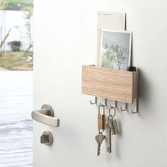 Say calm, cool, and collected with the Rin Magnet Key Hook by Yamazaki.  Organization is effortless with this clean and modern key rack.  Powerful magnets adhere to any metal surface, like an office door or refrigerator.  This stylish piece, designed with steel and wood, has hooks for keys and a top shelf for mail, sunglasses, or any other easy access items.    Features: Strong magnets for placement ease Small and convenient Contemporary design