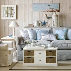 Seaside living room with white-washed wall panelling, a light blue sofa piled with cushions and an armchair, a coffee table chest and side table with lamp. Beach Cottage Style, Beach Cottage Decor, Coastal Cottage, Coastal Style, Coastal Decor, Seaside Decor, Nautical Style, Seaside Style, Coastal Farmhouse