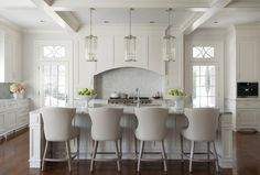 Elegant white kitchen boasts Robert Abbey Cole Pendants hung from a coffered ceiling above a white wainscoted island finished with a marble countertop seating light gray leather barstools facing an island sink with a polished nickel gooseneck faucet.
