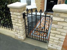 mosaic tile path with wrought iron rails yellow brick wall and slate paving london