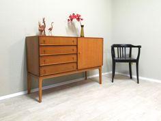 """Hier bieten wir ein besonders gut erhaltenes Vintage Möbel an: ein kleines Sideboard aus Teakholz, 60er Jahre aus deutscher Produktion im Dänischen Stil. Bei diesem schönen Stück ist alles aus Teakholz, sogar das Untergestell und die Möbelknöpfe! Das Möbel ist leicht geschliffen und geölt, es weist 2-3 klitzekleine Makel auf, kaum erwähnenswert. Für alle die ein""""Zwischending"""" zwischen Kommode und Sideboard suchen ist dieses Schmuckstück perfekt! #Sideboard #TeakSideboad"""