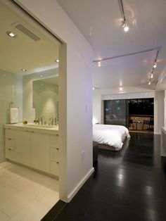 The master bathroom is totally renovated and incorporates a double-trough vanity, custom cabinetry and a wall of glass tile over a Thassos white floor.
