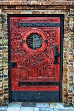 Porta de madeira, vermelha, com detalhes de metal e janela de vidro redonda.