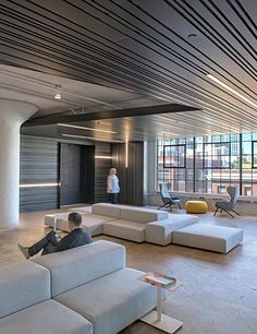 A floating ceiling plane of slatted metal visually unifies the offices and folds down onto vertical surfaces to define specific areas.