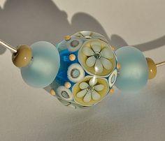 Majda Náhrdelník s autorskými vinutými perlami z mojí dílny navlečenými na kovové obruči z obec. kovu stříbrné barvy. Možno vyměnit za lanko. Velikost hlavní květinové vinutky je 25x19mm.