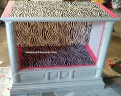 I repainted and used zebra fabric and pink duct tape to repurpose an old tv console for my daughters room to use for her American Girl Dolls.  I just need to add the handles.