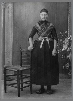 Vrouw in Staphorster streekdracht. Ze draagt opknapdracht en is waarschijnlijk in de lichte rouw. Op haar hoofd een ondermuts, zilveren oorijzer met spiraalvormige krullen aan de uiteinden en om het oorijzer een oorijzerband. Over de borstrok draagt ze een kraplap en een geruite schouderdoek, verder een schort met gedessineerd schortstukje en schoenen met zilveren gespen. 1890-1910 #Overijssel #Staphorst