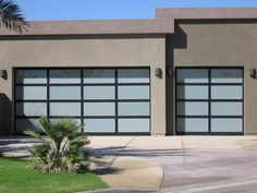 The intriguing Frosted Glass Garage Door with black anodized Steel Frame makes this simple modern home look so prestigious.
