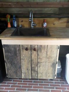 Copper sink, brick floor, reclaimed wood walls & cabinets