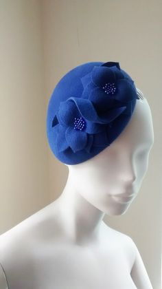 Gorgeous cocktail hat in a periwinkle blue velour felt. Two handmade flowers with hand beaded centers and a twirl of velour finish the hat. Hand