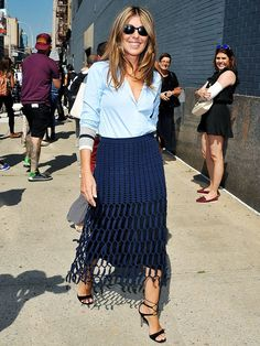 Nina Garcia in a blue oxford, skirt and strappy heels.